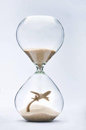 reloj de arena: Los viajes de verano. Reloj de arena que cae la arena tomando la forma de un avión despegando