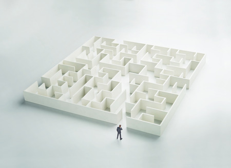 Business challenge. A businessman at the entrance to a maze. Rear view