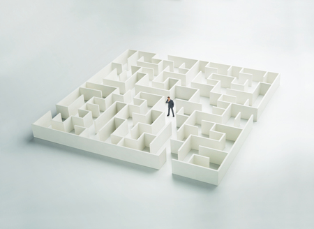 decisionmaking: Business challenge. A businessman navigating through a maze. Front view
