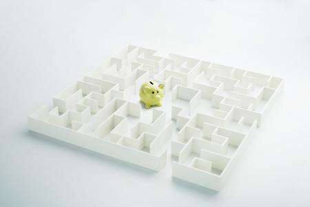 loveheart: The uncertainty of money and business. Piggy bank hidden inside a maze