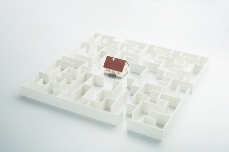 Real estate labyrinth. Toy house hidden inside a maze