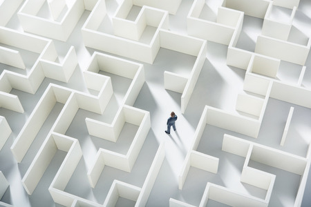 confusion: Business challenge. A businessman navigating through a maze. Top view