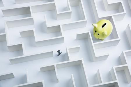 Businessman searching for piggy bank hidden inside a maze