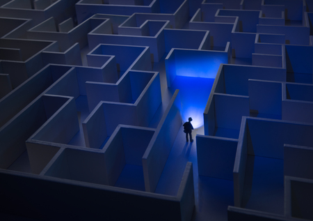 Businessman with flashlight walking through maze
