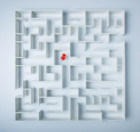decisionmaking: Red location direction pin in the middle of a maze, a symbol of searching for success Stock Photo
