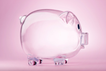 Empty transparent piggy bank on pink background Stock Photo