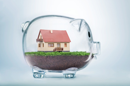 savings goals: Saving to buy a house or home savings concept with model house inside transparent piggy bank