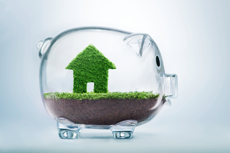 sales bank: Saving to buy a house or home savings concept with grass growing in shape of house inside transparent piggy bank Stock Photo