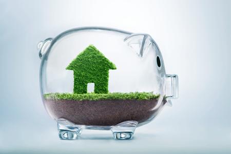 pieniądze: Zapisywanie kupić dom lub domu koncepcję oszczędności z trawy rosnące w kształcie domu wewnątrz przezroczystej skarbonki
