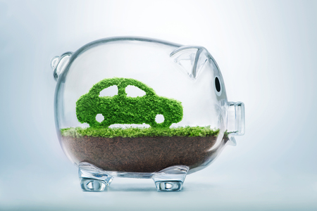 Green energy concept with grass growing in shape of car inside transparent piggy bank Reklamní fotografie - 52519565