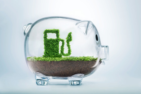 alternative: Green energy concept with grass growing in shape of fuel pump inside transparent piggy bank
