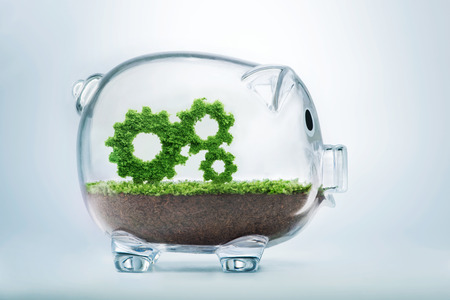 merging together: Business growth concept with grass growing in shape of gears inside transparent piggy bank Stock Photo