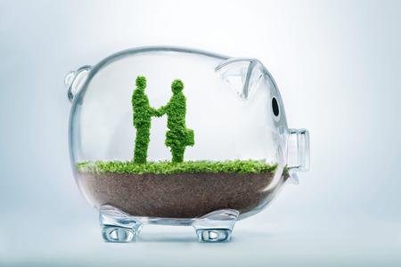 透明な貯金箱の中に草揺れ 2 人のビジネスマンの形で成長しているビジネス契約の概念がハングアップします。