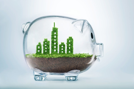 desarrollo económico: Concepto sostenible del desarrollo urbano con la hierba que crece en forma de una ciudad dentro de la hucha transparente Foto de archivo