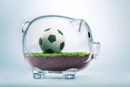 winning bid: Money and football business concept with soccer ball inside transparent piggy bank