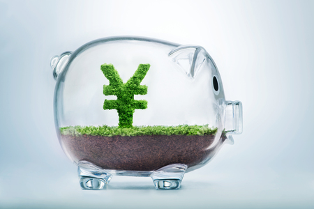 Piggy bank savings concept with grass growing in shape of Yuan sign