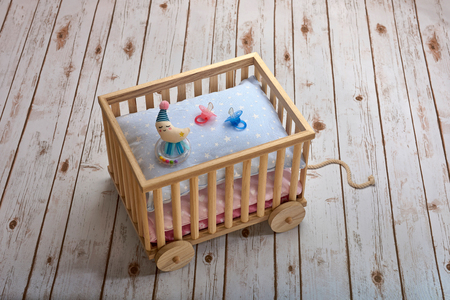 pull toy: Pink and blue pacifiers and a moon shaped baby rattle on pillows, in a toy cart