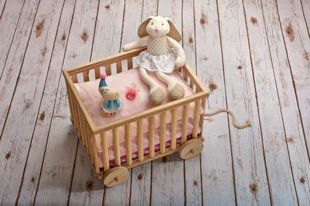 A bunny doll, a pink pacifier and a moon shaped baby rattle on pillows, in a toy cart