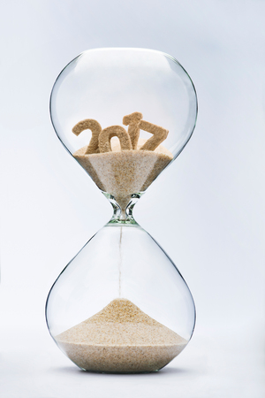 New Year 2018 concept. Time running out concept with hourglass falling sand from 2017. Stock Photo