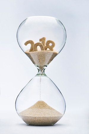 turn of the year: New Year 2019 concept. Time running out concept with hourglass falling sand from 2018.
