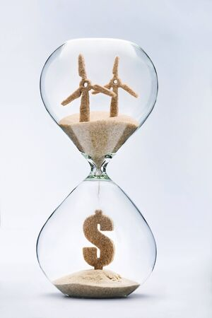 Time for clean energy concept with falling sand taking the shape of a wind turbine and dollar symbol inside a hourglass