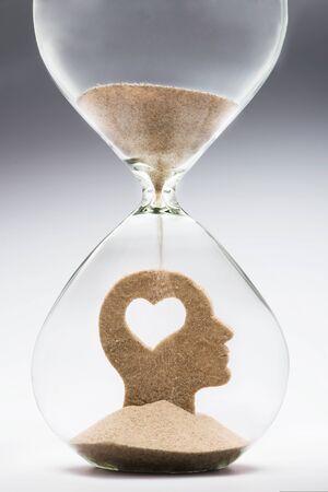 모래 시계 안에 인간의 머리 안쪽에 잘라내어 심장 모양을 복용 떨어지는 모래와 개념을 사랑하는 학습 스톡 콘텐츠