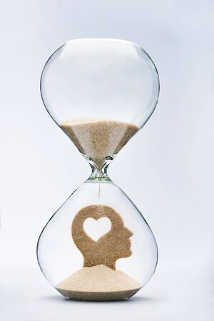 Learning to love concept, with falling sand taking the shape of a cut out heart inside a human head, inside a hourglass