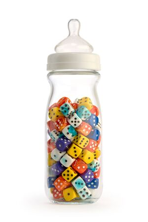 Child raising gambling concept. Isolated baby bottle filled with colorful dice. Stock Photo