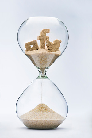 Social media content lost in the sea of information concept, symbolised by the falling sand inside a hourglass Stock Photo