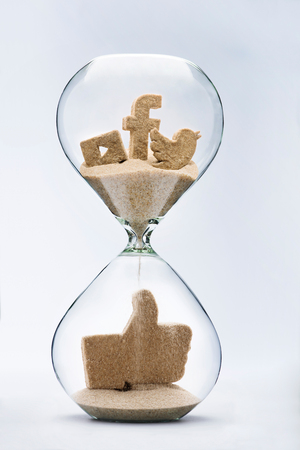 Social media concept, with falling sand taking the shape of a thumbs up inside a hourglass Stock Photo