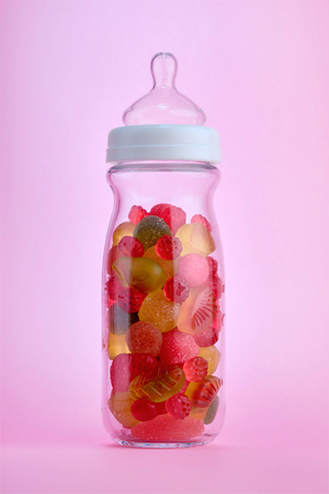unnatural: Unhealthy baby food concept. Baby bottle filled with colorful jellies to highlight the excess of sugar in childrens diet.