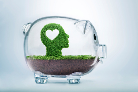Love is the seed of our being. Grass growing in the shape of a cut out heart inside a human head, inside a transparent piggy bank, symbolising the care, dedication and investment needed for our love to grow.  Stok Fotoğraf