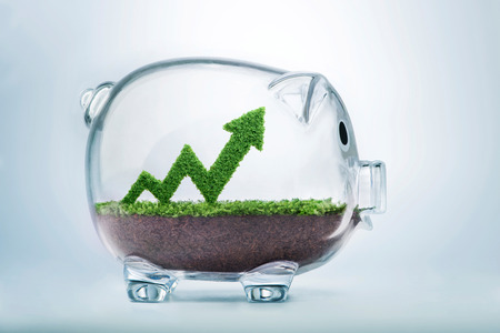 Grass growing in the shape of an arrow graph, inside a transparent piggy bank, symbolising the care, dedication and investment needed for progress, success and profit in business.