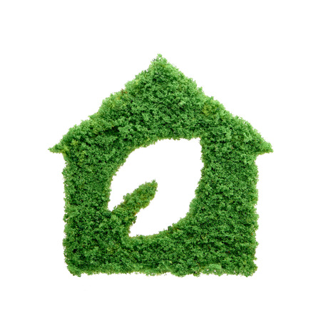 Nature is home concept. Grass growing in the shape of a house with a cut out leaf. Build sustainable homes and protect the environment. Stock Photo