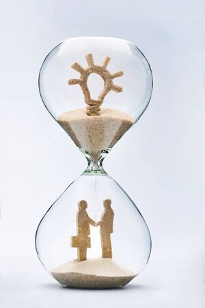 Creativity and innovation in business concept. Two businessmen shaking hands made out of falling sand from light bulb flowing through hourglass.