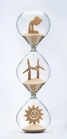 Time for clean energy concept with falling sand taking the shape of a factory, a wind turbine and the Sun inside a hourglass.