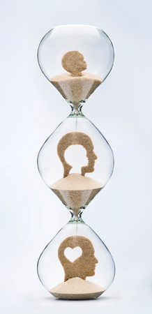 Childhood is the root of adulthood. Self evolution concept. Falling sand inside a hourglass taking the shape of a mans head in various stages.