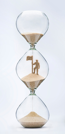 Time is success concept with falling sand taking the shape of a businessman with flag on mountain top inside a hourglass Stock Photo