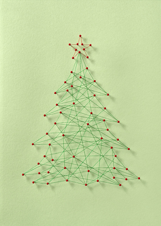 Celebrating Christmas together. Network of pins and threads in the shape of a Christmas tree symbolising sharing and community.