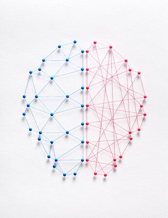 Network of pins and threads in the shape of a brain symbolising two different types of logic. Rational vs irrational concept.