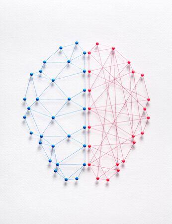 Netzwerk aus Nadeln und Fäden in Form eines Gehirns, das zwei verschiedene Arten von Logik symbolisiert. Rationales vs. irrationales Konzept. Standard-Bild