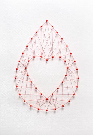 Donate blood concept. Network of pins and threads in the shape of a blood drop symbolising group effort and collaboration for saving lives. Reklamní fotografie