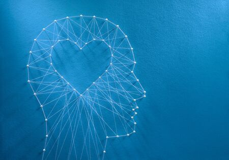 Learning to love concept. Network of pins and threads in the shape of a cut out heart inside a human head symbolising that love is the core of our being and has its own logic.
