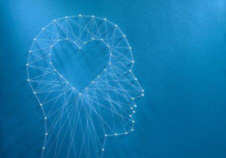 Leren om van concept te houden. Netwerk van spelden en draden in de vorm van een uitgesneden hart in een menselijk hoofd dat symboliseert dat liefde de kern van ons wezen is en zijn eigen logica heeft.