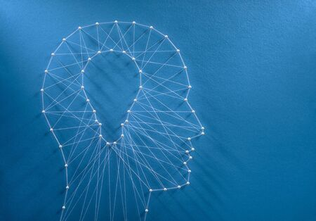 Inspiration concept. Network of pins and threads in the shape of a cut out light bulb inside a human head symbolising creative thinking. Reklamní fotografie