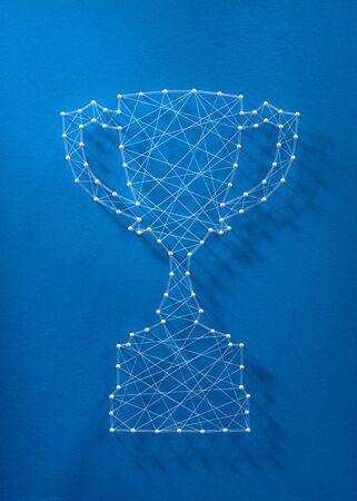 Sieć szpilek i nitek w kształcie pucharu z trofeum symbolizującego współpracę na rzecz sukcesu.