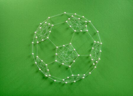 Football supporters concept. Network of pins and threads in the shape of a soccer ball symbolising teamwork success.