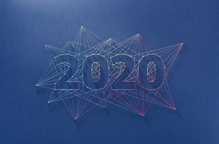 Celebrating the new year together. Colorful network of pins and threads in the shape of the year 2020 symbolising community and team effort in building the future.
