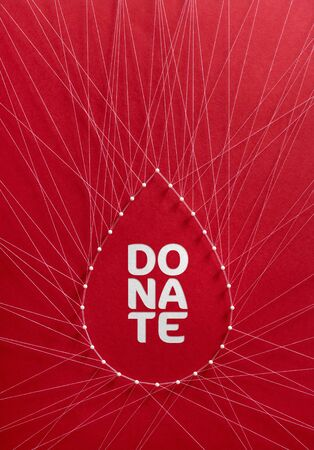 Donate blood concept. Network of pins and threads in the shape of a blood drop symbolising group effort and collaboration for saving lives. Фото со стока