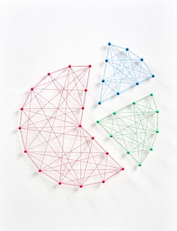 Network of pins and threads in the shape of a business pie graphic chart symbolising teamwork analysis.